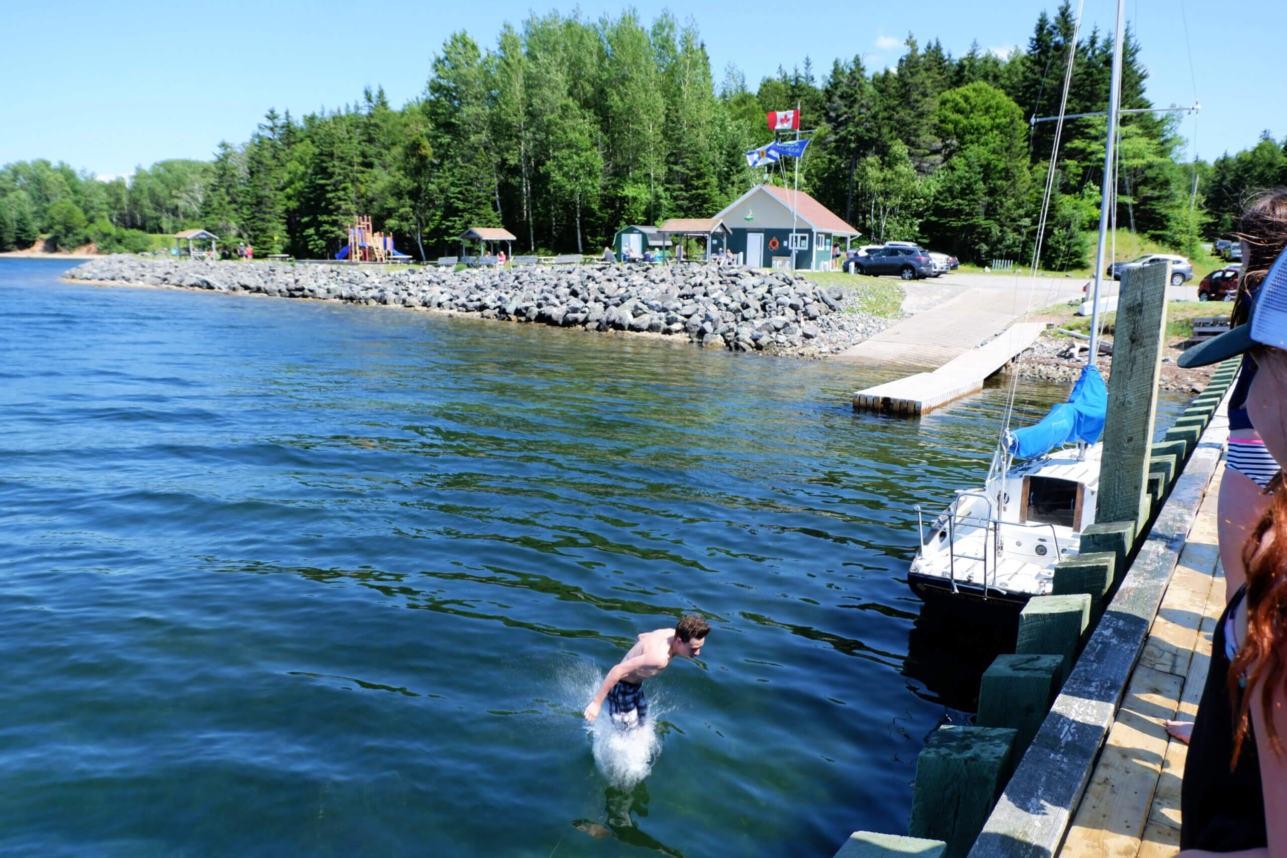 teen jumping off wharf at ross ferry marine park playground cape breton nova scotia