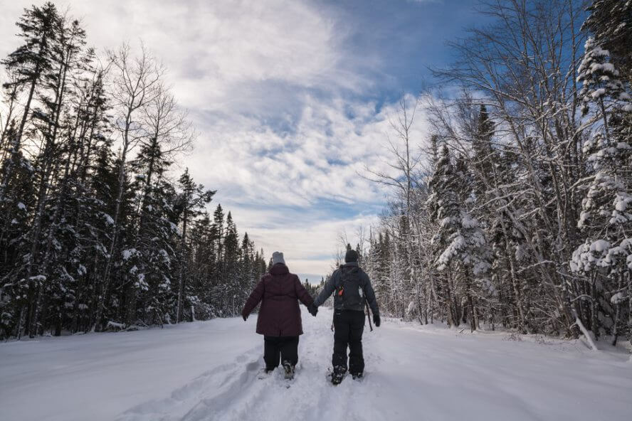 couple walking on snowshoes for riverview winter carnival new brunswick