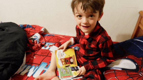 young boy reading in bed weird but true national geographic kids books review non-fiction canada animals christmas early literacy reading momsmeet pickle planet moncton telephone bedtime