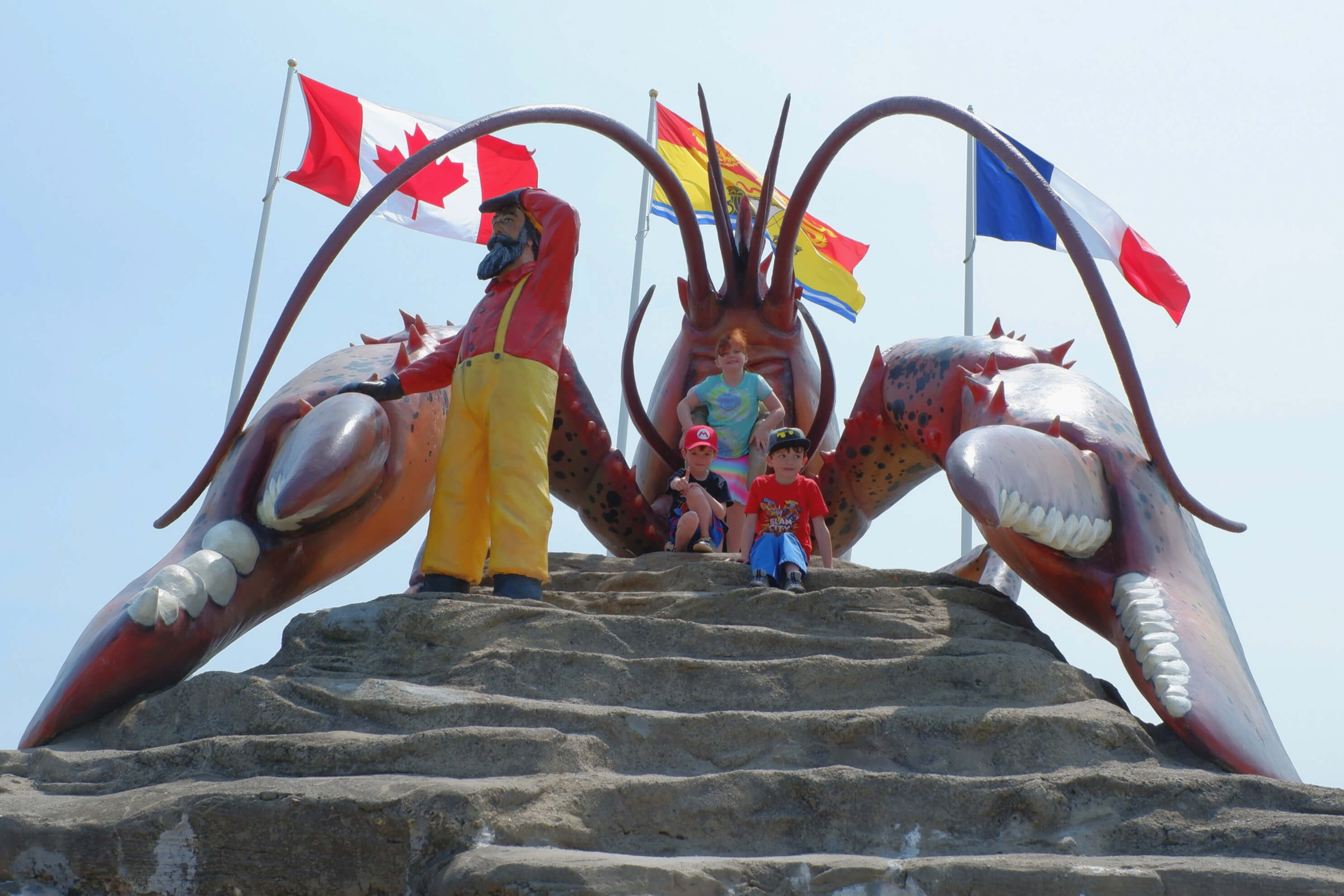 children with the world's largest lobster statue in shediac, new brunswick