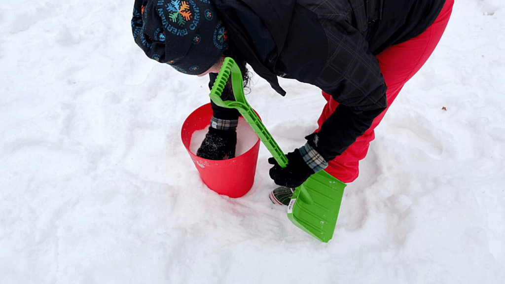 using a shovel and trash can to pack snow for sculpting a gnome