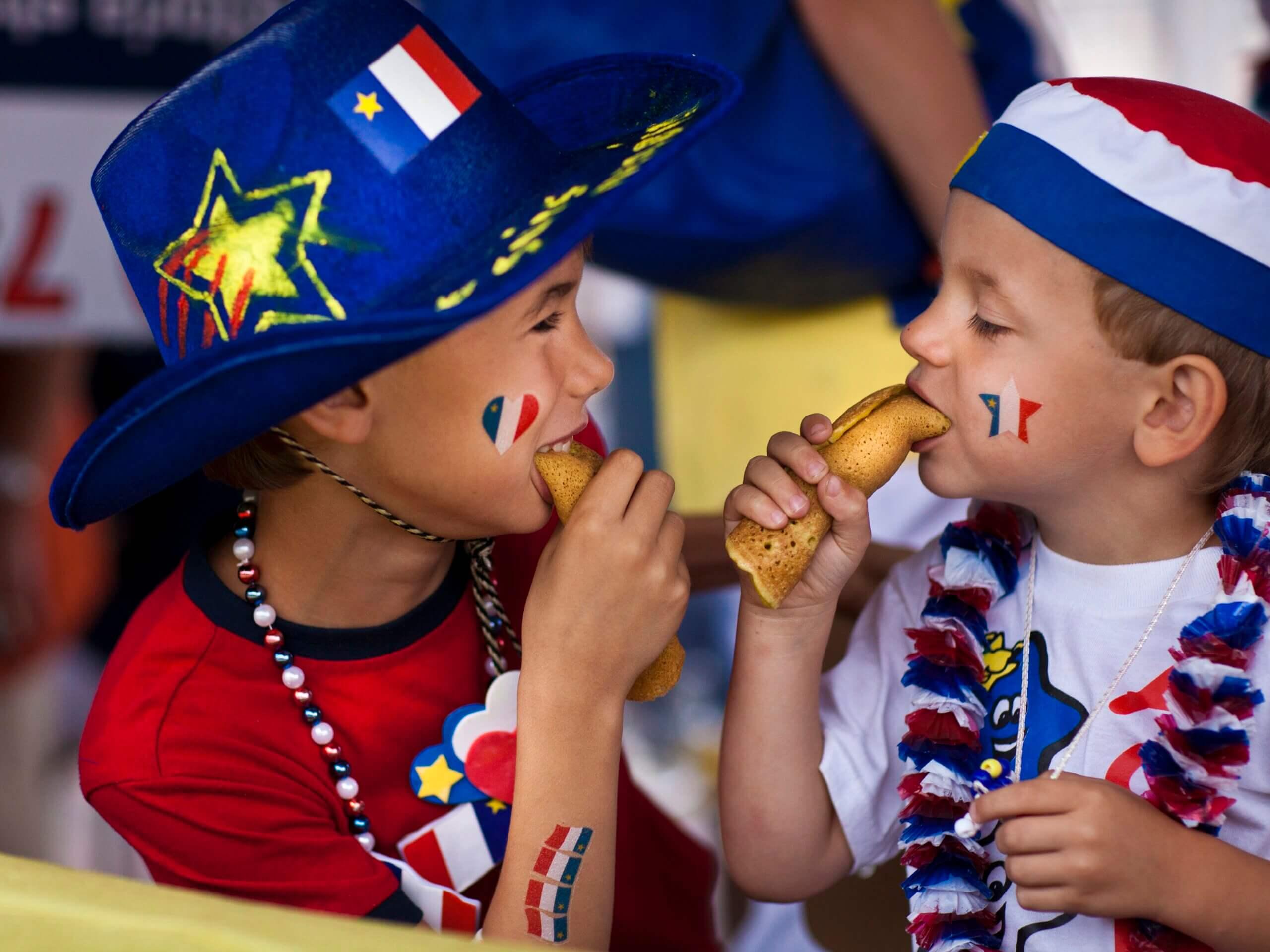 New Brunswick Tourism photo of Children eating ployes at Tintamarre Enfants qui mangent des ployes, Festival Acadien de Caraquet