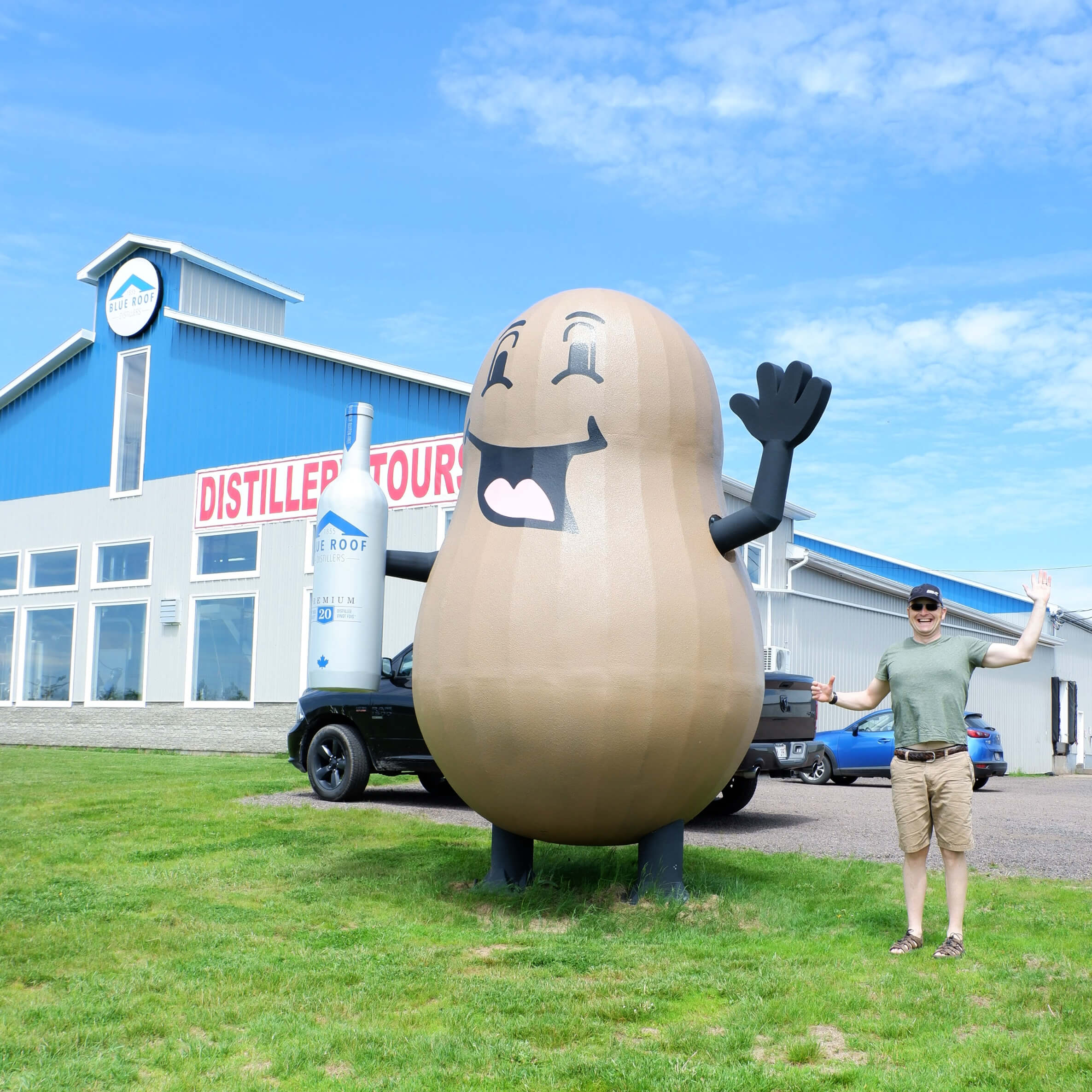 pickle planet papa next to the giant potato holding a bottle of vodka at blue roof distillers in new brunswick
