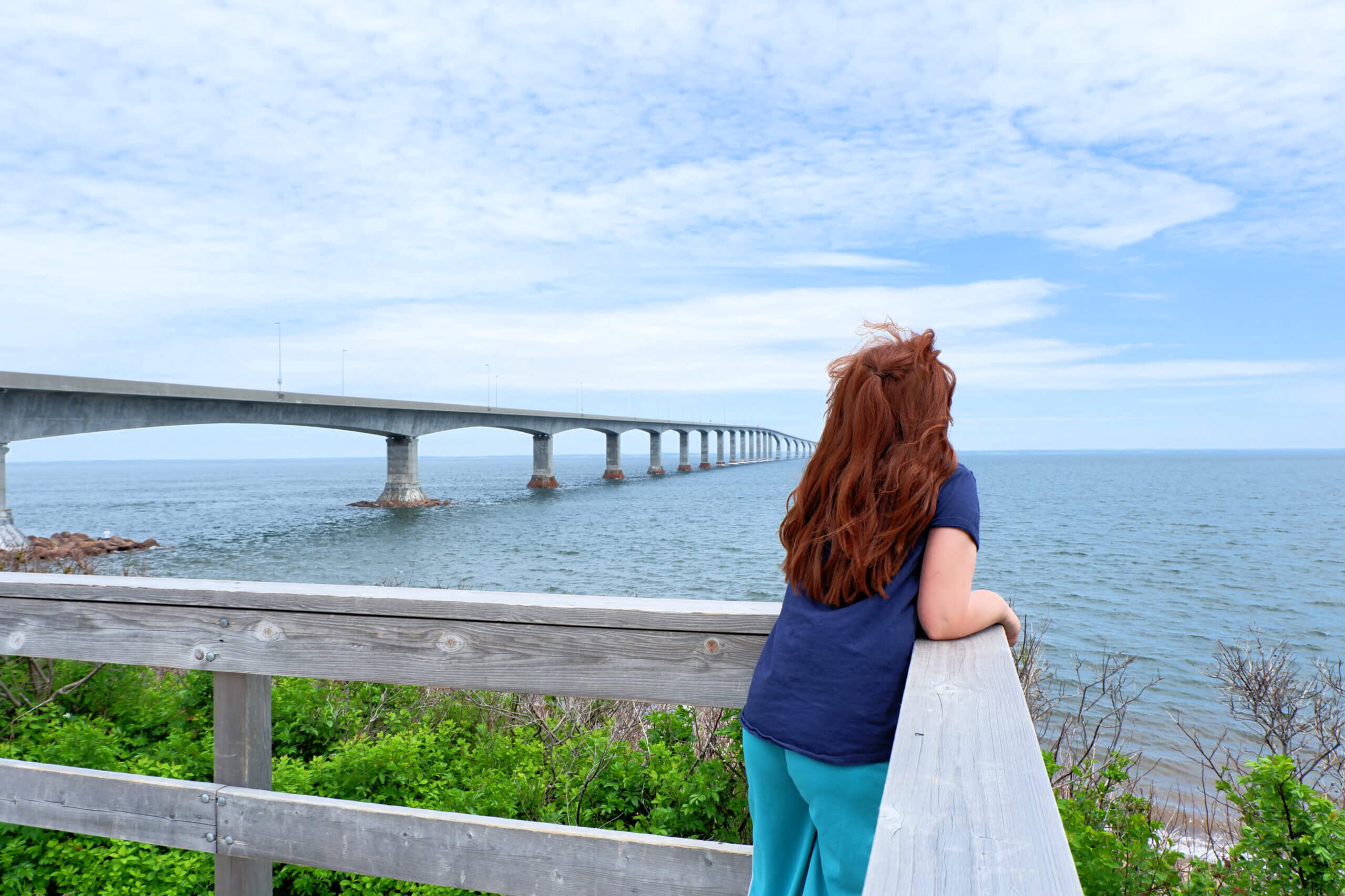 red haired girl looking at out the confederation bridge linking new brunswick and prince edward island pickle planet moncton