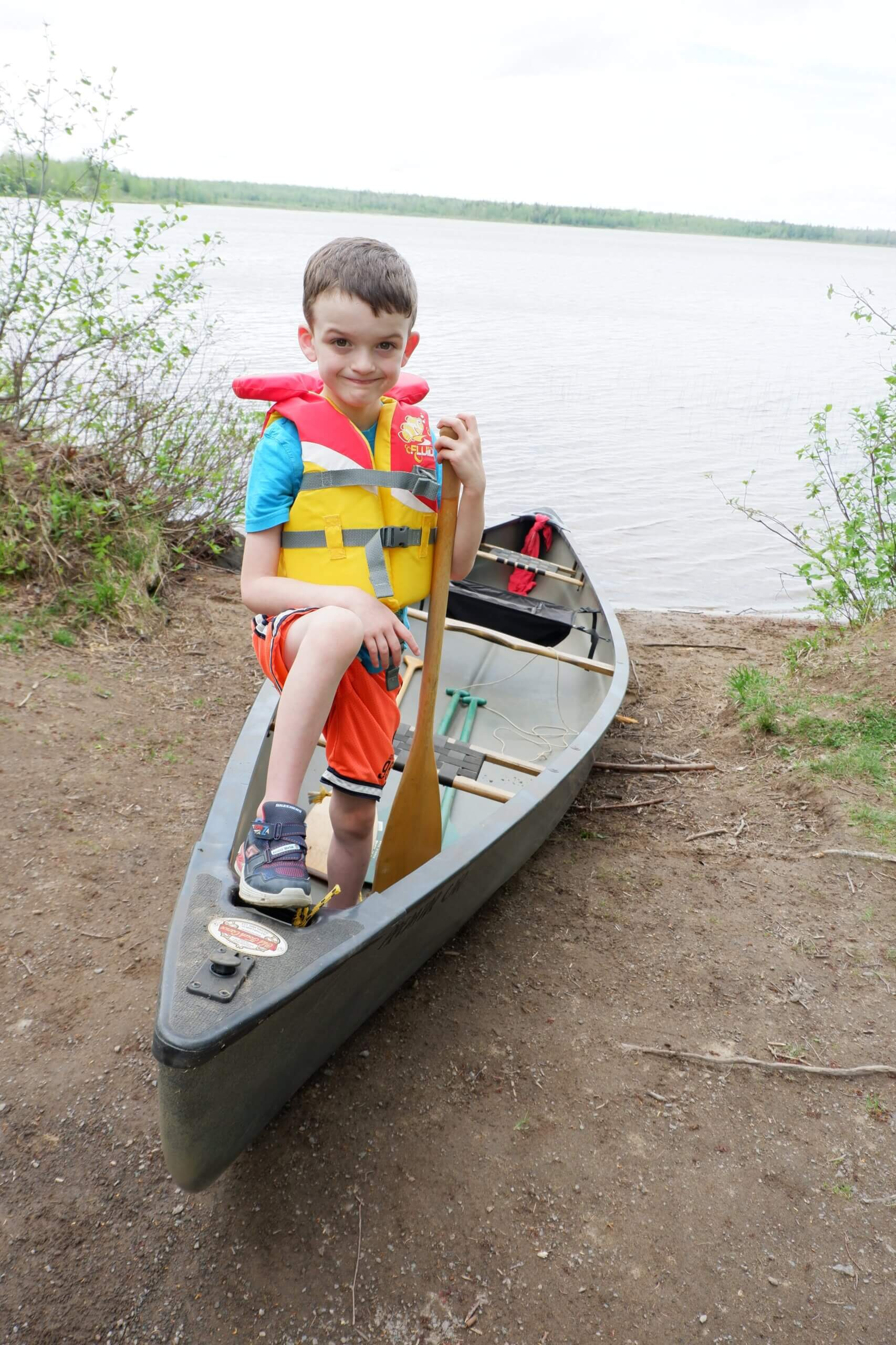pickle planet kid in a canoe on the shores at irishtown park