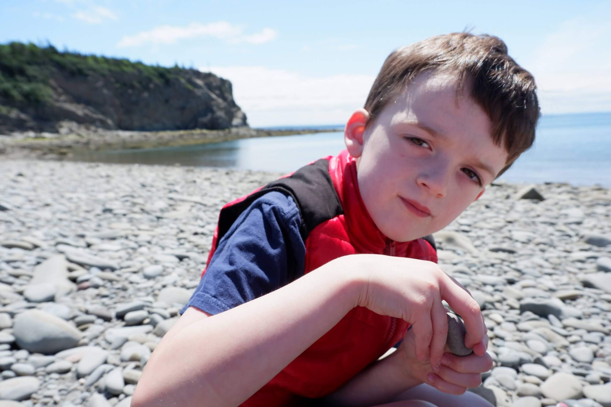 young boy on beach with rocks fossils cape enrage new brusnwick