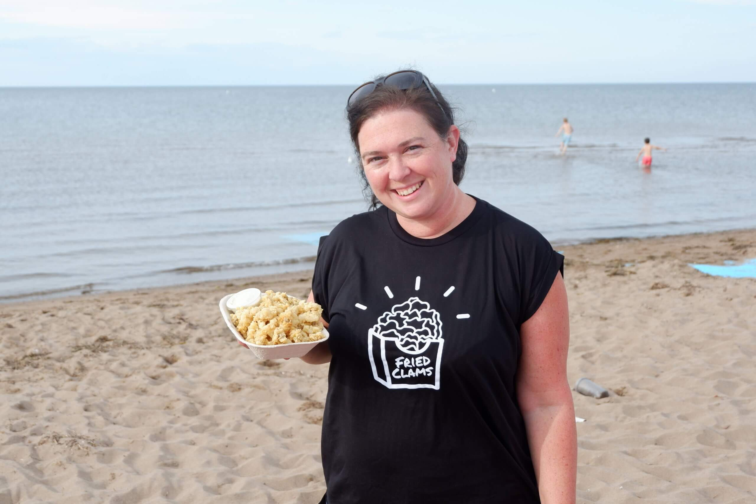 pickle planet's jenna morton enjoying fried clams in her fried clams t-shirt on aboiteau beach in new brunswick