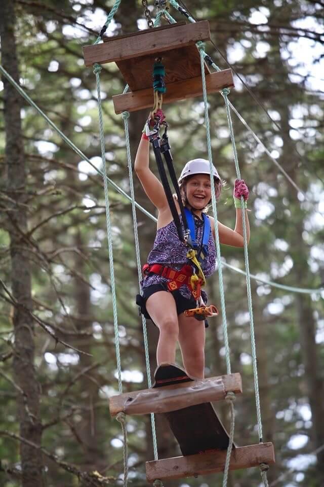 woman climbing in trees at timber top adventures saint john