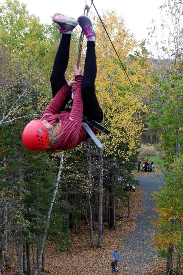 woman ziplining across the miramichi river